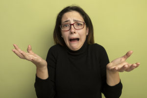 upset young beautiful girl in a black turtleneck and glasses looking at camera shrugging shoulders yelling standing over light background